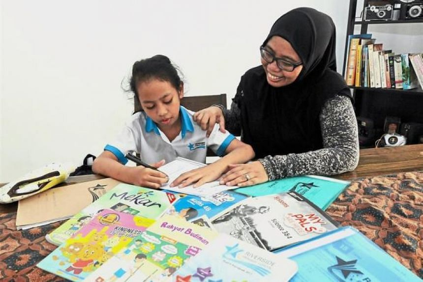 Hard at work: Ms Noraini Mokhtar (right) helping her daughter Aleesha with her homework after she returns from school in Singapore at their home in Taman Majidee, Johor Baru.