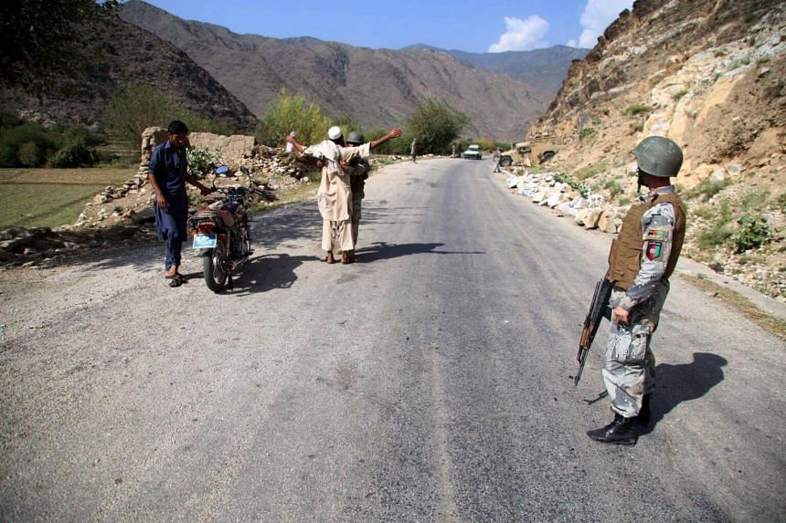Afghan security officials stand guard on a highway near the area where a US drone reportedly targeted in the Diwagai area of Siwaki district of Kunar province, Afghanistan on Oct 13, 2017.