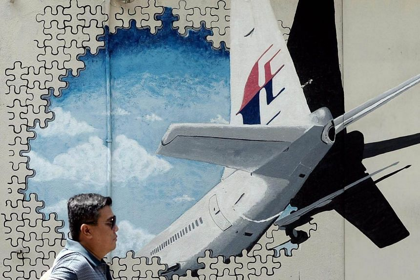 A Malaysian man walks in front of a mural of missing Malaysia Airlines MH370 plane in a back-alley in Shah Alam. Malaysia, Australia and China ended a A$200 million deep-sea search for the plane in January without any trace being found.