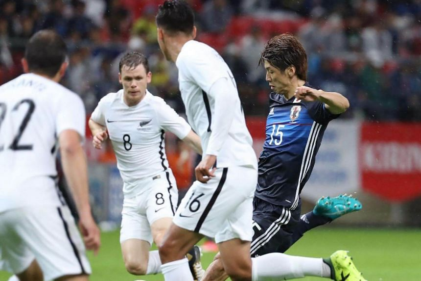 Japan's forward Yuya Osako (right) shoots the ball among New Zealand's Andrew Durante, Michael McGlinchey and Dane Ingham during their friendly football match in Toyota city, Aichi prefecture on Oct 6, 2017.