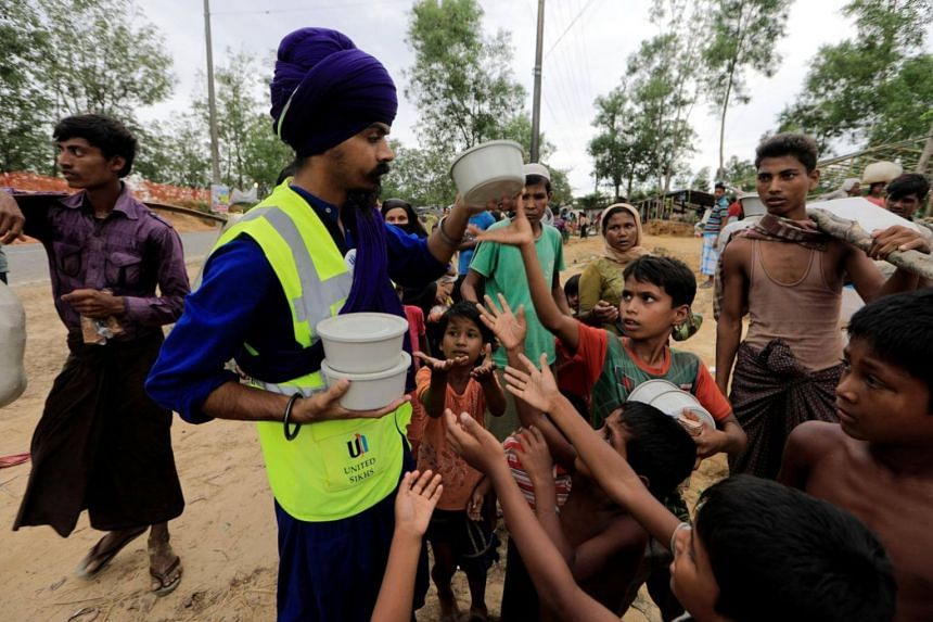 Rohingya refugees receive food on the road after they received permission from the Bangladeshi army to continue their way to Kutupalong refugee camps, near Cox's Bazar in Bangladesh on Oct 19, 2017.
