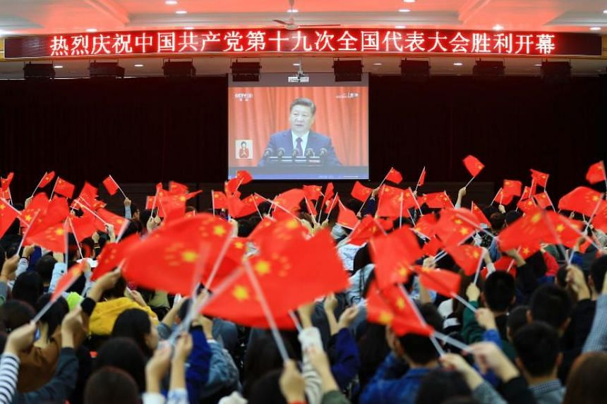 College students wave national flags as they watch the opening of the 19th Communist Party Congress in Huaibei.