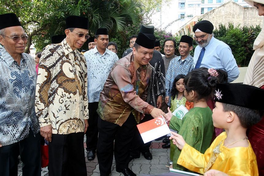 Tuanku Syed Faizuddin Putra Jamalullail (centre), crown prince of Perlis, shaking hands with children from Jamiyah childcare centre during his visit to Singapore.