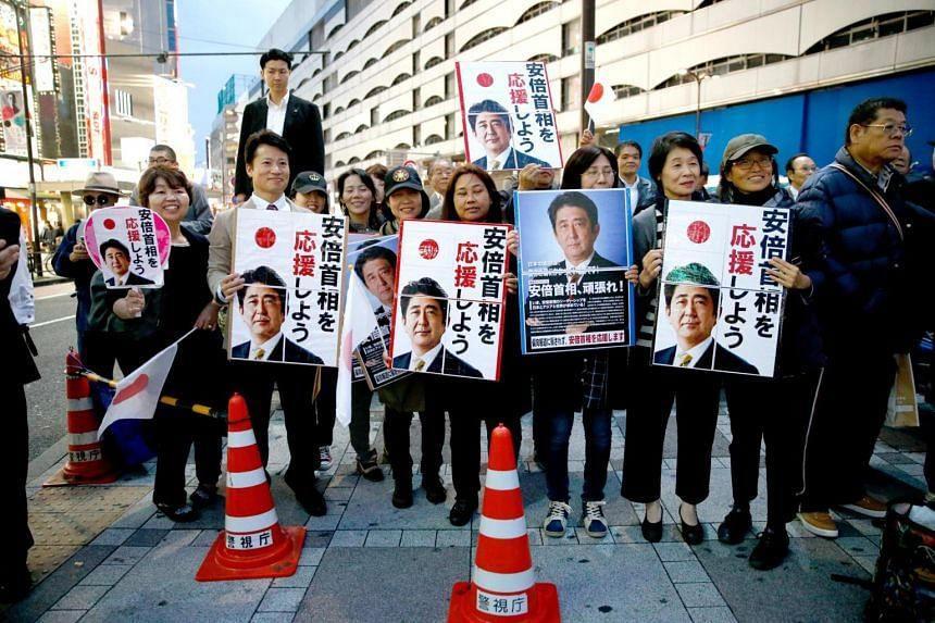 Supporters of Japan's Prime Minister Shinzo Abe, who is also the ruling Liberal Democratic Party leader, wait for him at an election campaign rally in Tokyo, Japan on Oct 18, 2017.