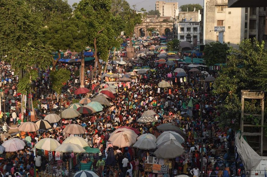 Indian shoppers throng the ancient Teen Darwaja marketplace.