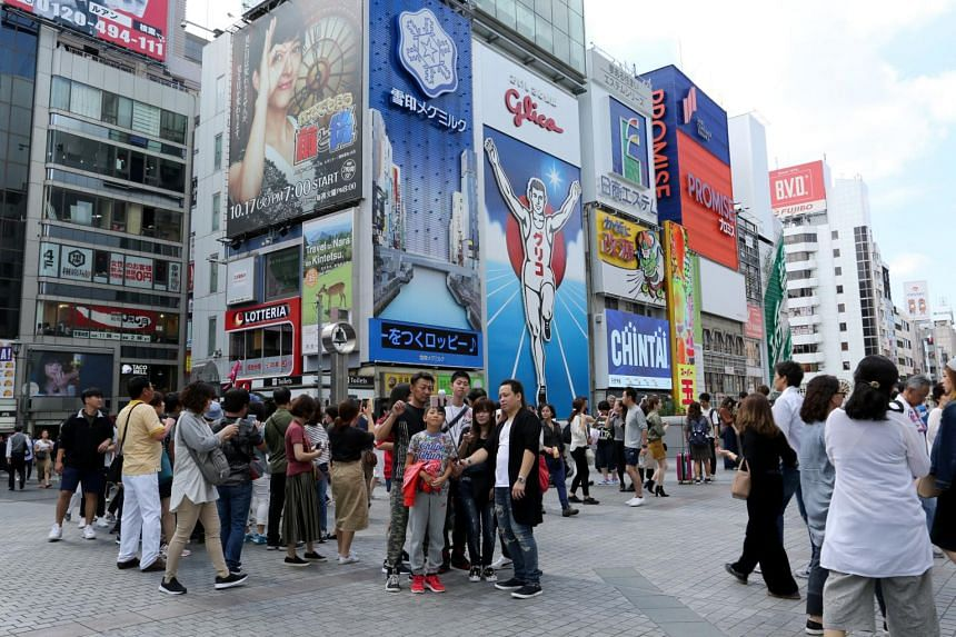 People gather in front of an advertisement in the Dotonbori district of Osaka.