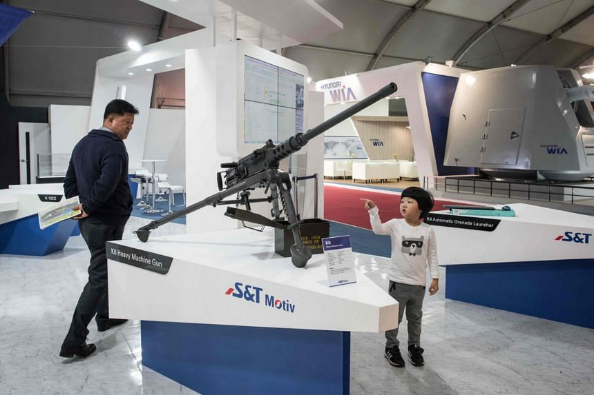 A child pointing towards a K6 heavy machine gun made by South Korean automotive and defence company S&T Motiv at the Seoul International Aerospace and Defense Exhibition (ADEX) in Seongnam, south of Seoul, on Oct 16, 2017.