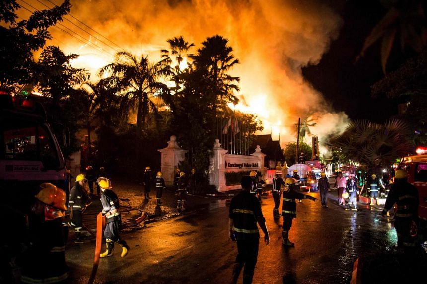 Firefighters work at the scene of a fire at Kandawgyi Palace hotel in Yangon early on Oct 19, 2017.