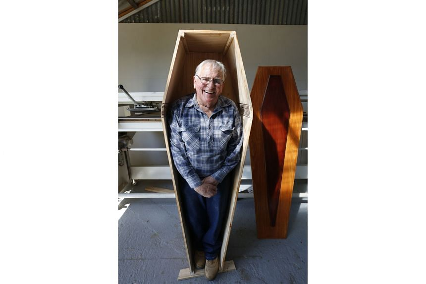 Mr Russell Game, 79, posing on Tuesday in his self-made coffin at the Community Coffin Club in Ulverstone, northern Tasmania. His wife is making the lining for the coffin, which is still to be finished. The coastal town of about 7,000 inhabitants boa