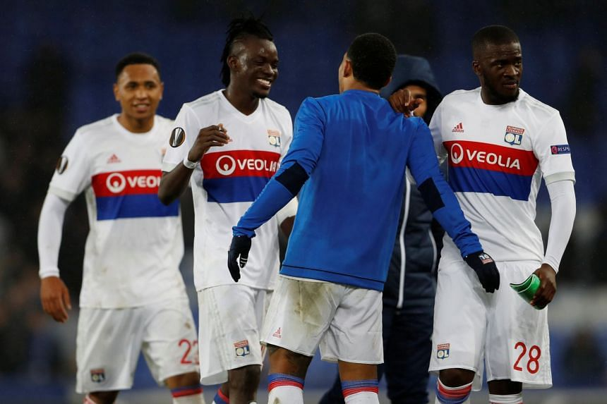 Lyon's Bertrand Traore celebrates after the match with Memphis Depay and Tanguy Ndombele.