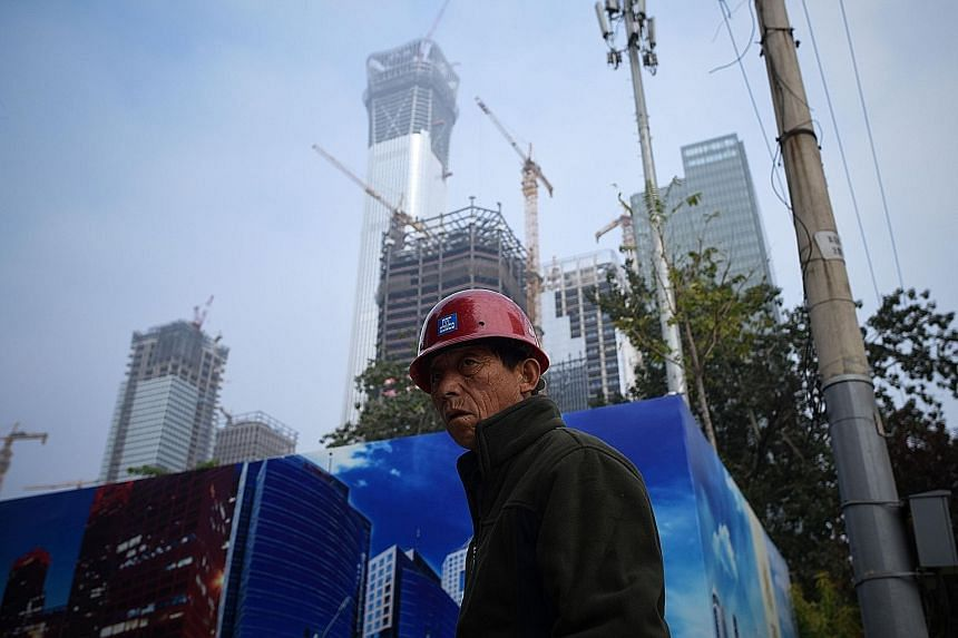 A worker outside a construction site in Beijing's Central Business District on Tuesday. New construction starts by floor area in China rose just 1.4 per cent on the year last month, slowing from a 5.3 per cent increase in August.