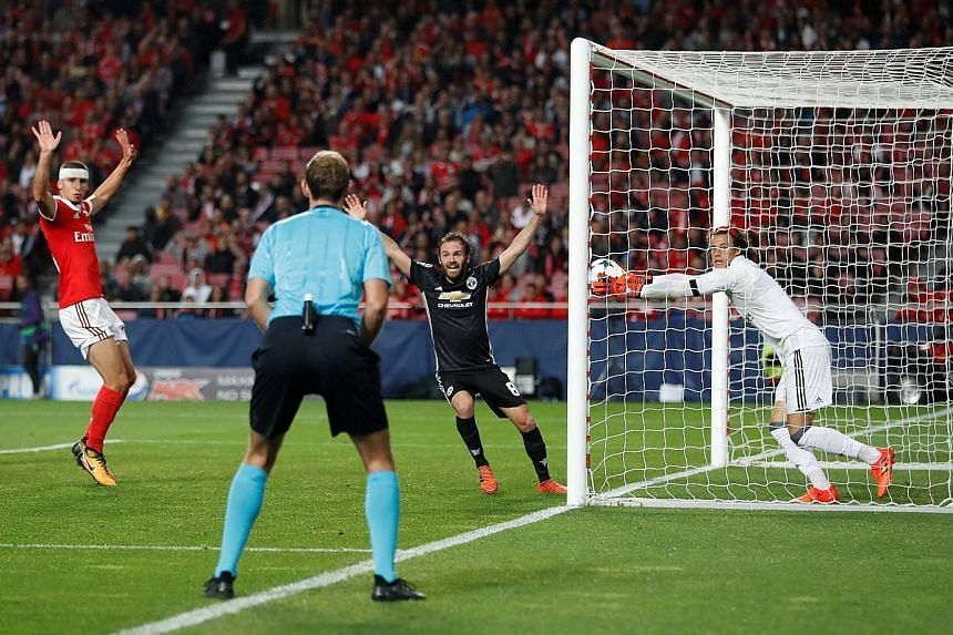 Benfica's 18-year-old goalkeeper Mile Svilar carrying the ball over the line despite stopping a free kick by Marcus Rashford (not pictured). The error gave Manchester United a 1-0 win in the Champions League Group A game.