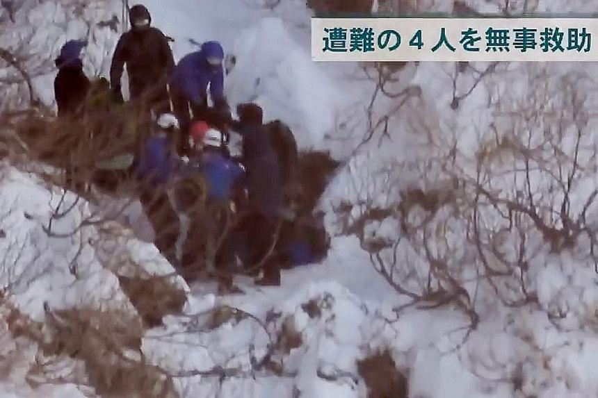 Rescuers are seen in a video grab with the four stranded hikers, including Singaporean Amelda Lim and her Malaysian husband Long Ji Yung, as they get ready to be airlifted from Asahidake early Wednesday morning.
