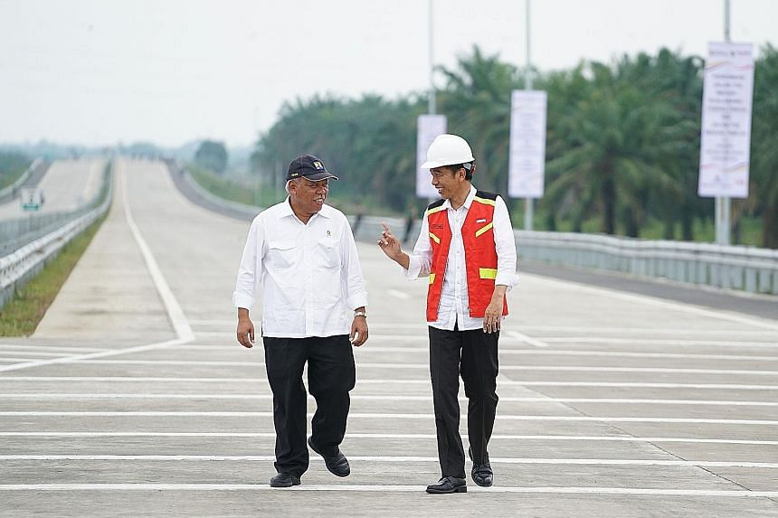 Indonesia's President Joko Widodo (right) speaking with Minister of Public Works and Housing Basuki Hadimuljono during the inauguration of the Medan-Kualanamu-Tebing Tinggi toll road last Friday.