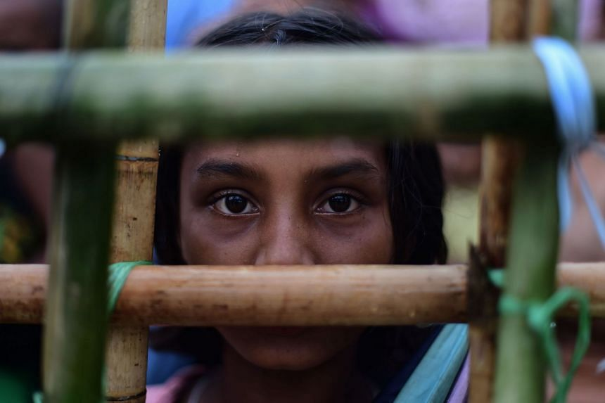 A Rohingya refugee girl waits to collect relief materials at Thyangkhali refugee camp in Teknaf.