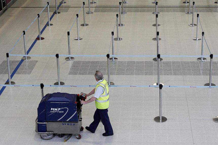 An airport worker cleans around empty check-in desks in a terminal in Manchester Airport, in England, on April 16, 2010.