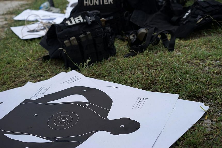 Target sheets, bulletproof vests and ammunition are seen on the ground as Thai police from the Narcotics Suppression Bureau Division 3 undergo firearms training at a camp in Hua Hin, southern Thailand.