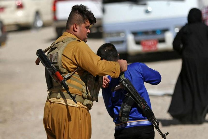 A member of the Iraqi Kurdish forces straps a kalashnikov riffle on the back of a youth at an unfinished housing project where displaced people fleeing violence in the northern Kirkuk province are taking shelter on Oct 19, 2017 in Arbil, the capital