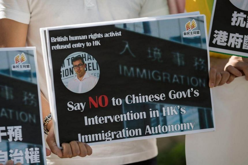 An activist holds a sign showing a photo of barred British Conservative Party activist Ben Rogers during a protest outside Hong Kong's Central Government Offices in Hong Kong, China on Oct 13, 2017. Mr Rogers was denied entry to Hong Kong on Oct 11.