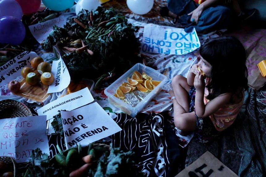 """A child sits next to a sign reading """"Food Pellets are not meals"""" during a protest against Sao Paulo Mayor Doria's plans to serve school meals made of reprocessed food pellets in Sao Paulo, Brazil on Oct 19, 2017."""