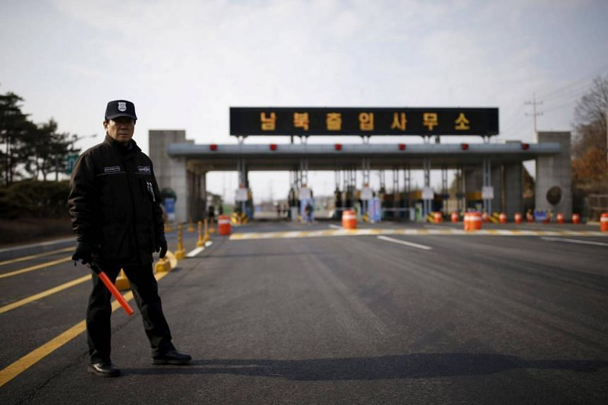 A South Korean security guard stands guard on an empty road which leads to the Kaesong Industrial Complex (KIC) in Paju, South Korea on Feb 11, 2016.