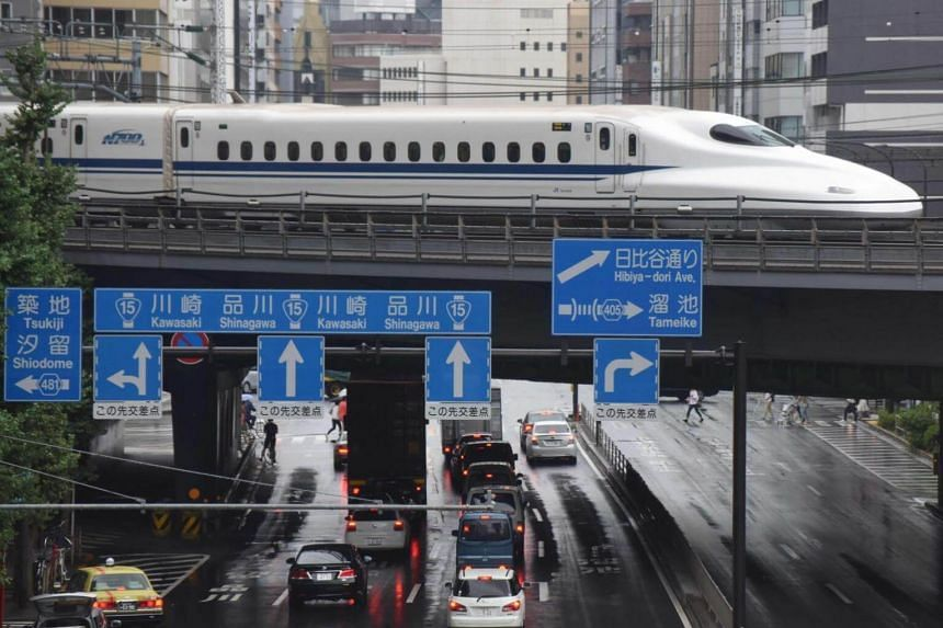 A Shinkansen bullet train moves on tracks above traffic in Tokyo on Aug 14, 2017.