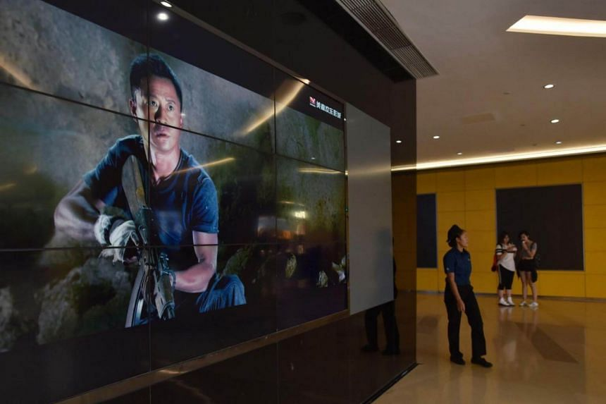 A woman walks past a screen showing scenes from Wolf Warrior 2 in Beijing on Aug 21, 2017.  Wolf Warrior 2 depicts a Chinese hero fighting Western mercenaries in a war-torn African country.
