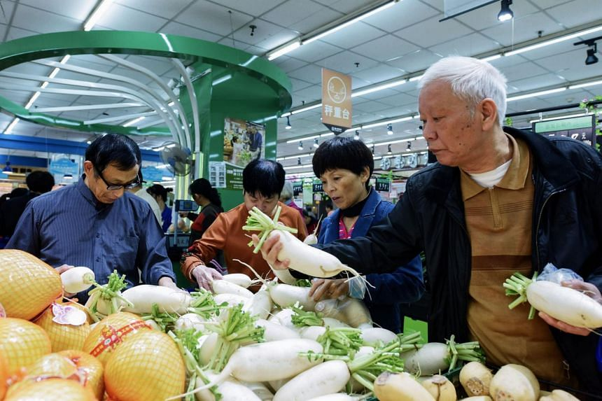 Customers buy fruits and vegetables at a supermarket in Hangzhou, east China's Zhejiang province on Oct 16, 2017.
