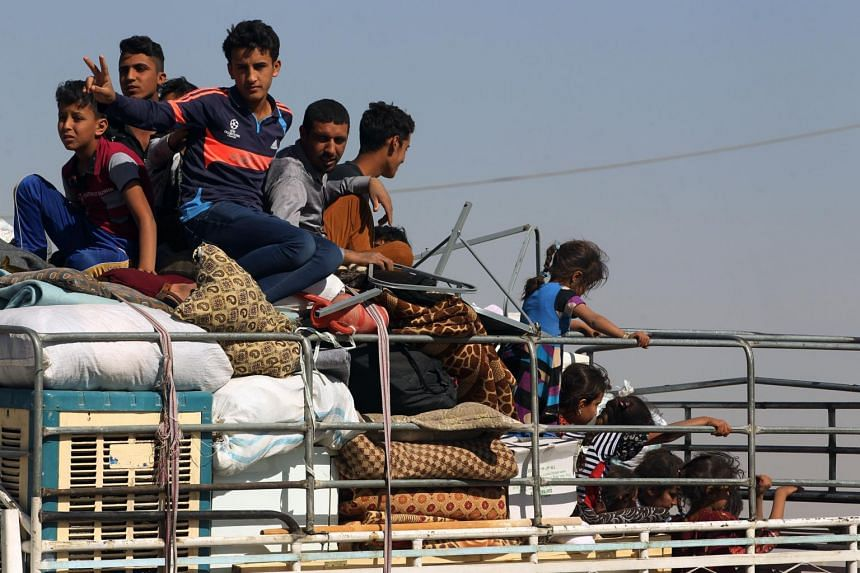 Displaced Iraqis, who fled from Hawija in 2014 to Kirkuk, riding in vehicles as they return to Hawija, after the town was retaken by Iraqi forces.