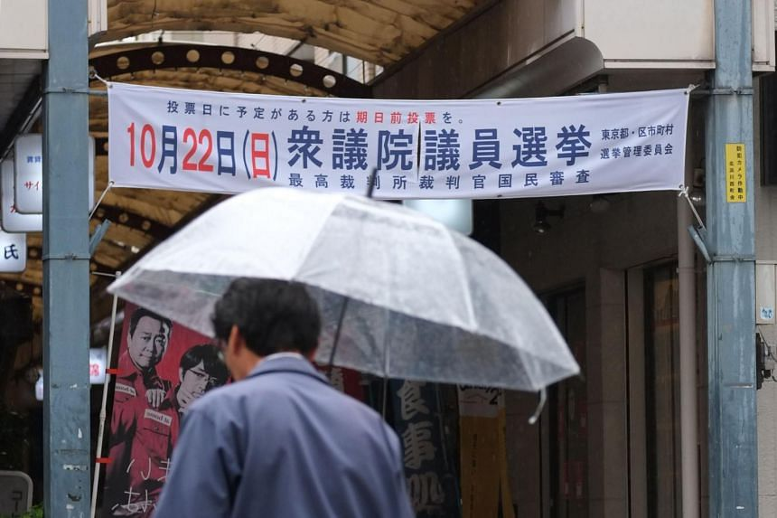 A pedestrian walking past a banner encouraging participation in the upcoming Oct 22 general election in Tokyo's Shinagwa ward.