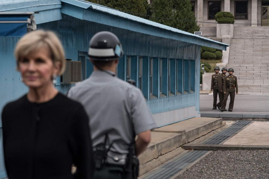 North Korean soldiers (rear) watch as Australia's Foreign Minister Julie Bishop (left) stands on the southern side of the military demarcation line between North and South Korea at the truce village of Panmunjom.