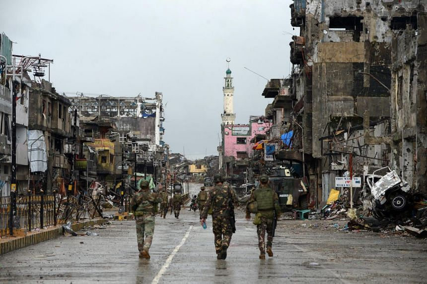 """Philippine soldiers walk past destroyed buldings in Bangolo district, after President Rodrigo Duterte declared Marawi City """"liberated"""", in Marawi on Oct 17, 2017."""