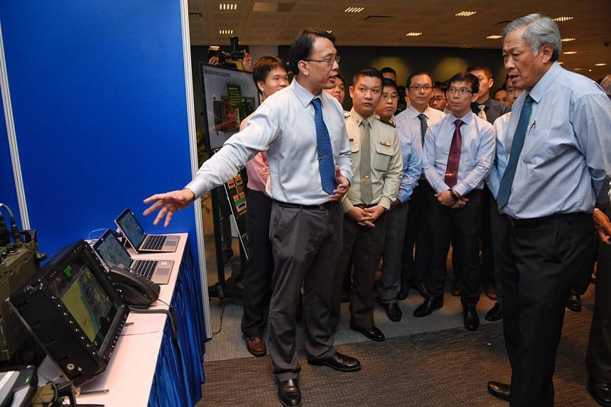 Team leader Hee Yong Siong of the Army C4IT Team shows Minister Ng Eng Hen some of the equipment used in the Secure Army Battlefield Internet during the Defence Technology Prize Awards Ceremony on Oct 20, 2017.