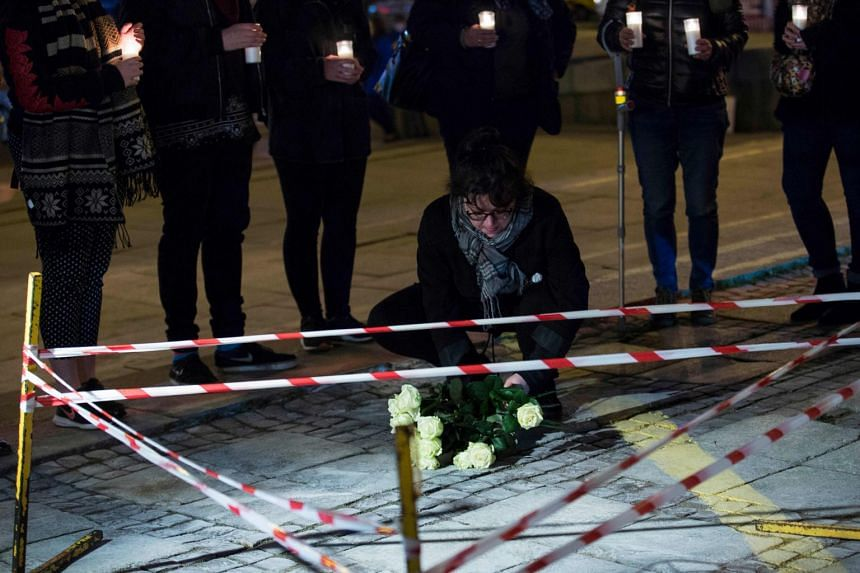 People hold a vigil in front of Warsaw's landmark Palace of Culture where a man set himself alight.