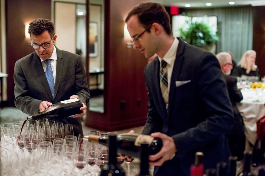 Sommeliers of Daniel Boulud's wine group Daniel Johnnes (left) and Josh MacGregor pour wines at Daniel, at a dinner to debunk some commonly-held wine myths. PHOTO: NYTIMES