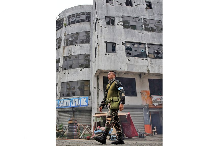 A soldier walking past a building in Marawi city that was damaged after troops cleared the area of pro-ISIS militant groups yesterday.