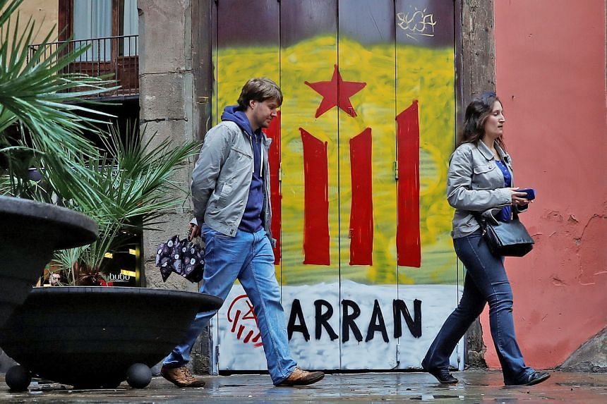 "A door in Barcelona painted with the colours of the Catalan separatist flag and the word ""Arran"", the name of a pro-independence leftist youth organisation. The Spanish government's decision to directly intervene in Catalonia is set to worsen the c"