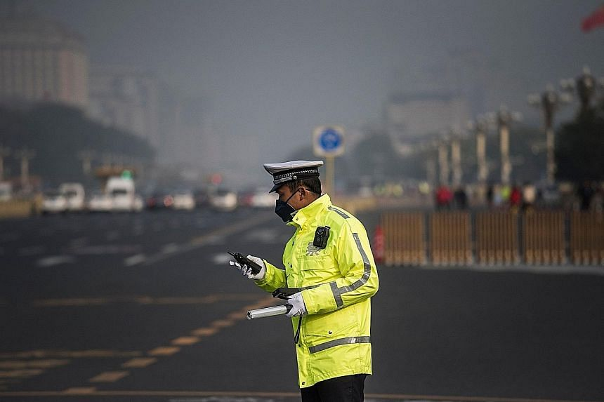 A policeman in a face mask at Tiananmen Square as smog enveloped Beijing yesterday, defying efforts to clear the air for the Chinese Communist Party's ongoing congress.