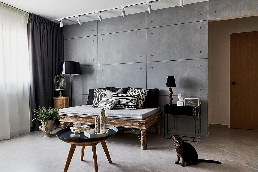 Concrete-looking tiles create a cement screed-vibe in the living room, which has a sofa the owner bought from fashion retailer British India.