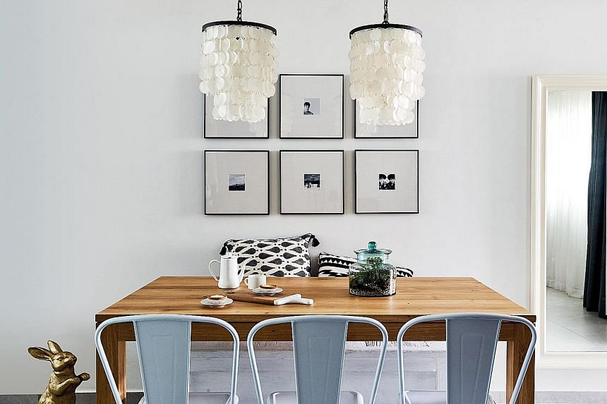 The dining area gets a rustic touch with a wooden table and pendant lamps made of seashells.