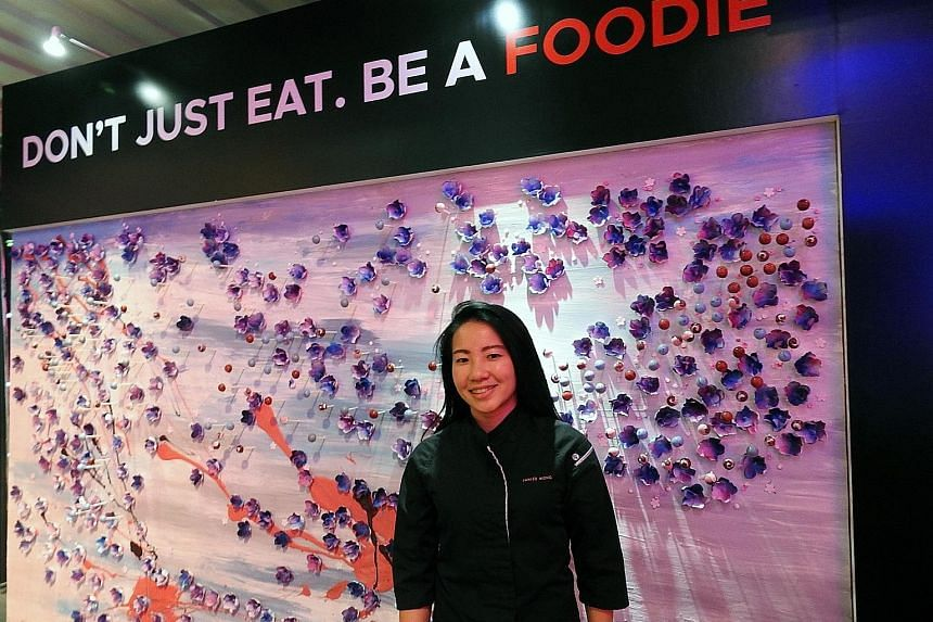 Singapore pastry chef Janice Wong with her dessert art wall showcasing the Republic's flora and fauna at the launch of the new STB brand campaign in Seoul yesterday. The wall features orchid-shaped sugar flowers and chocolate balls infused with gula