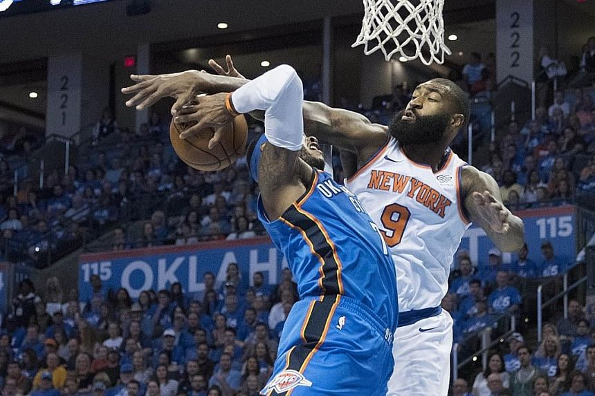 New York Knicks' Kyle O'Quinn (in white) trying to block Carmelo Anthony of the Oklahoma City Thunder during their NBA game on Thursday. Anthony ended with 22 points in his team's 105-84 victory.