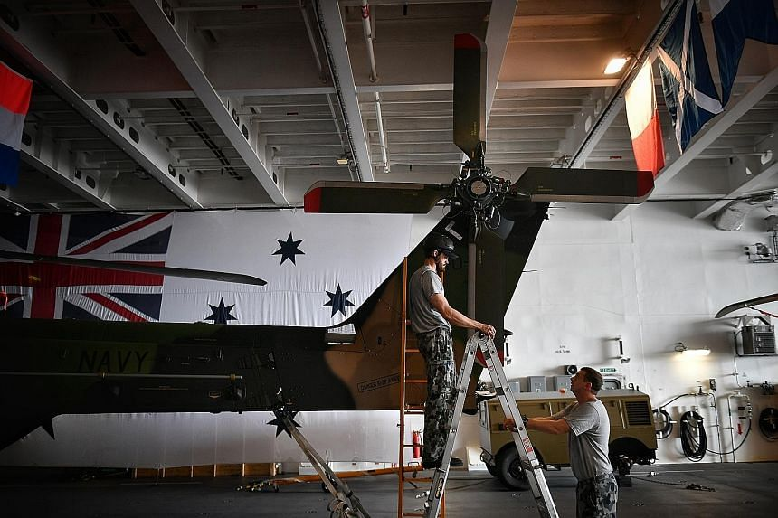 Members of the Royal Australian Navy working on an MRH-90 helicopter on board the HMAS Adelaide docked at Changi Naval Base. The Landing Helicopter Dock warship is the Australian navy's new amphibious vessel and was open to the media on its second da