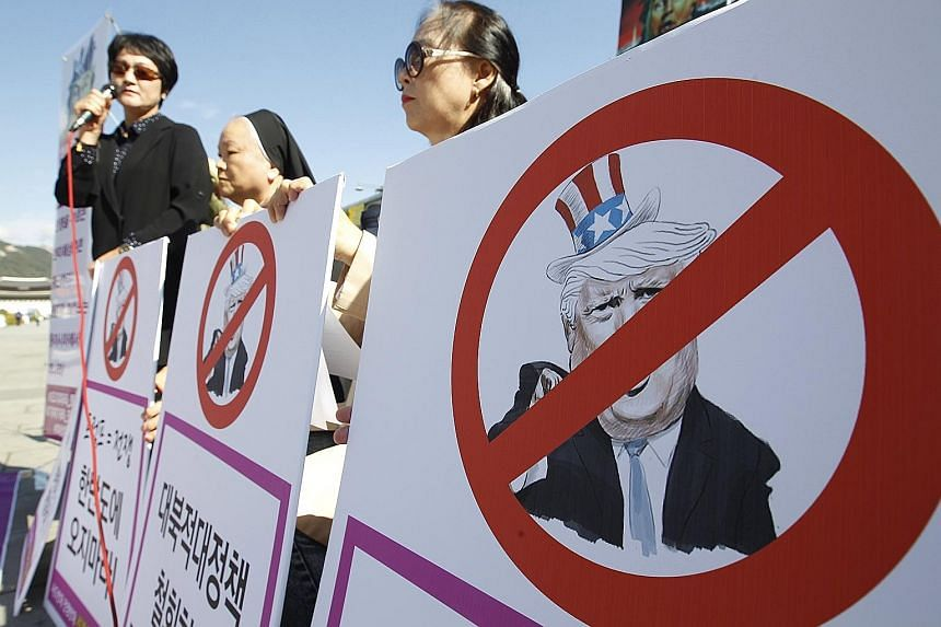 Civic activists with defaced portraits of US President Donald Trump during a rally outside the United States Embassy in Seoul on Thursday to protest against a joint American and South Korean naval exercise. South Korea is ramping up its defences agai