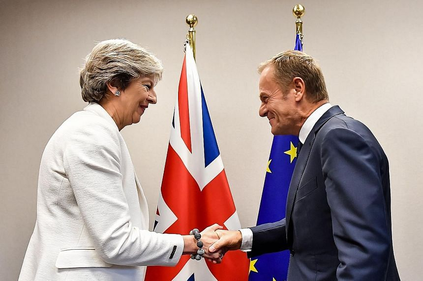 British Prime Minister Theresa May being welcomed by European Council President Donald Tusk for a bilateral meeting in Brussels yesterday. In a move that risks being seen as a snub to the EU's gesture, Mrs May insisted once again yesterday that a det