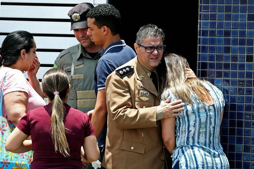 A Military Police officer comforts a woman at the scene of the shooting.