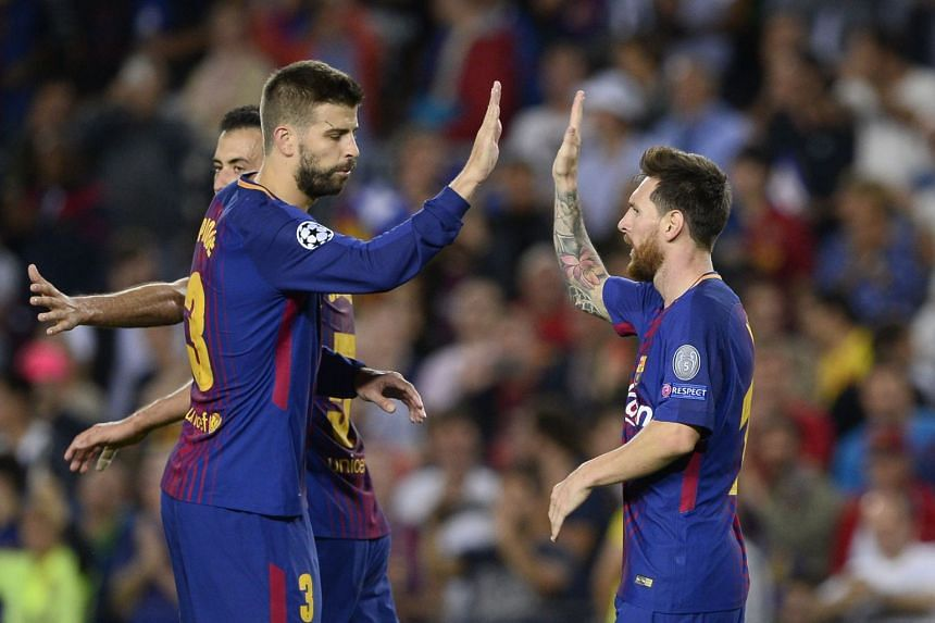 Barcelona players Gerard Pique (left) and Lionel Messi during a match.