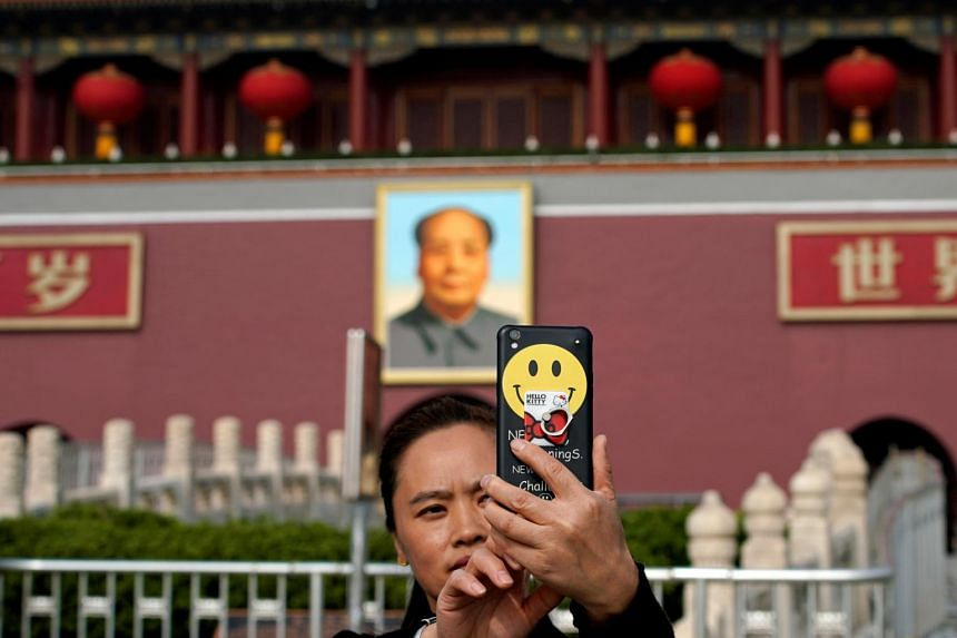 A woman takes a photograph in front of the Tiananmen Gate during the 19th National Congress of the Communist Party of China, in Beijing, China, on Oct 20, 2017.