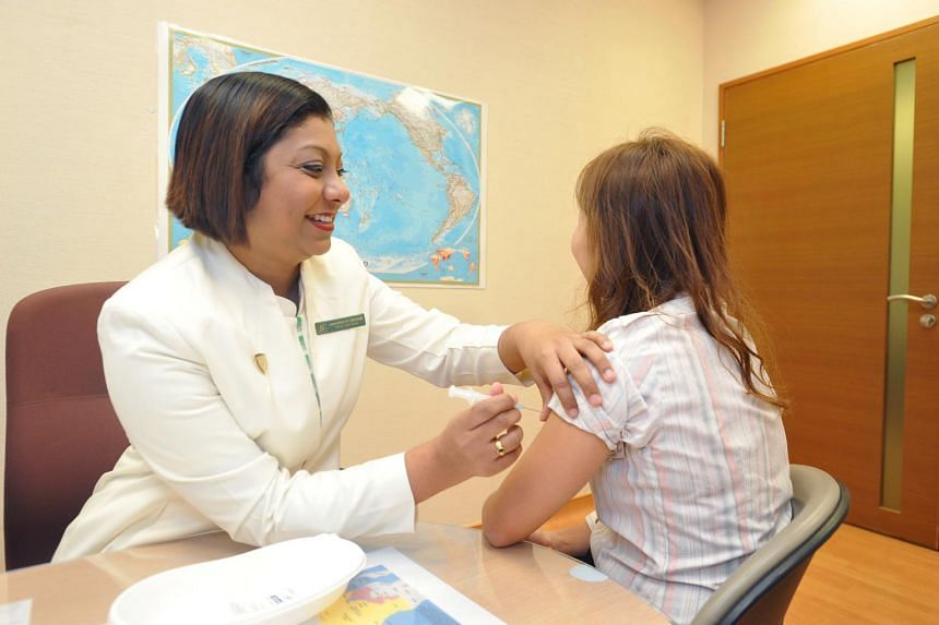 A file photo of senior staff nurse Asannachiyaar Chinnathamby, from the travel clinic at Singapore General Hospital, giving a vaccine injection to a patient in the clinic.