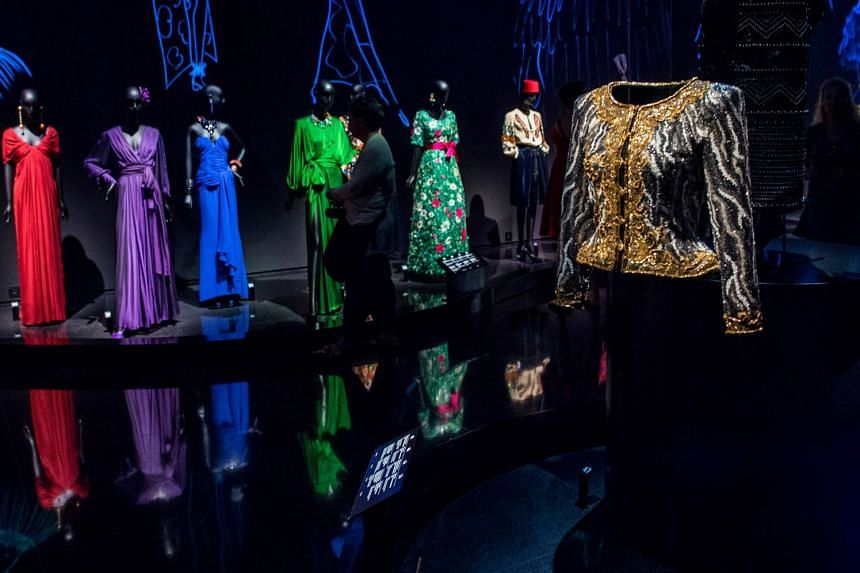 Outfits (above) and books are among the exhibits at the new Yves Saint Laurent museum.